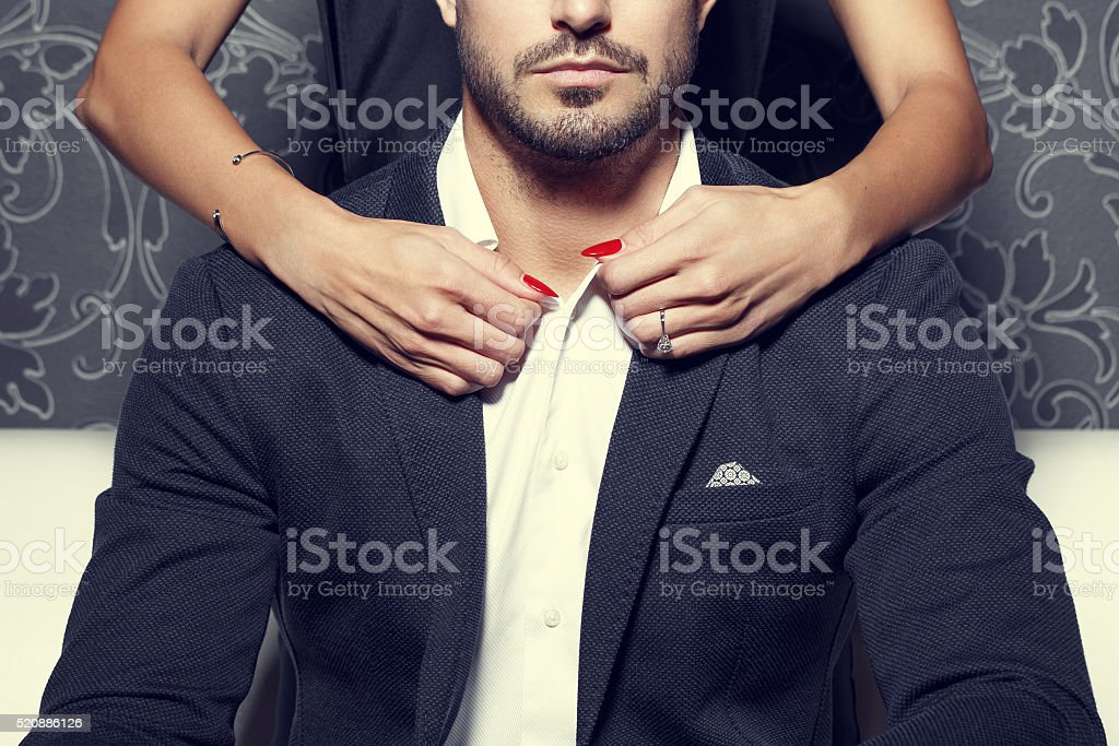 Woman hands undress rich man stock photo