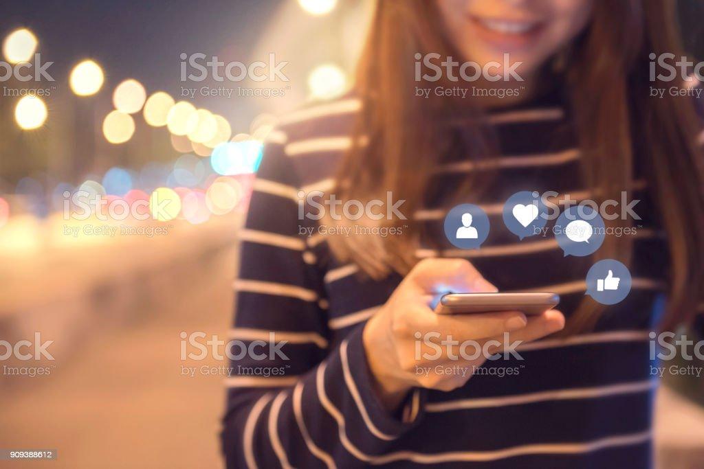 Manos de mujer con móvil smartphone en la calle con icono social media y redes sociales. - foto de stock