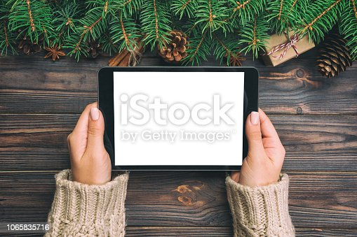 woman hands using tablet computer on wooden table bachground. cristmas shopping time. Happy Christmas mock up background, top view. vintage.