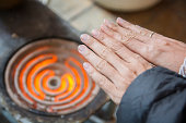 Woman Hands warming above hot stoves
