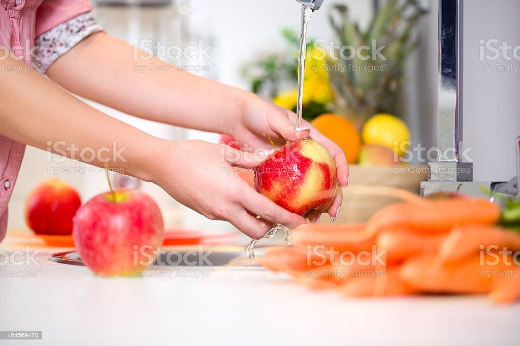 Woman hands washing tasty apple stock photo