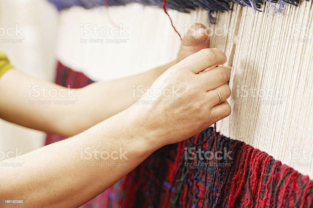 Woman hands weaving carpet stock photo