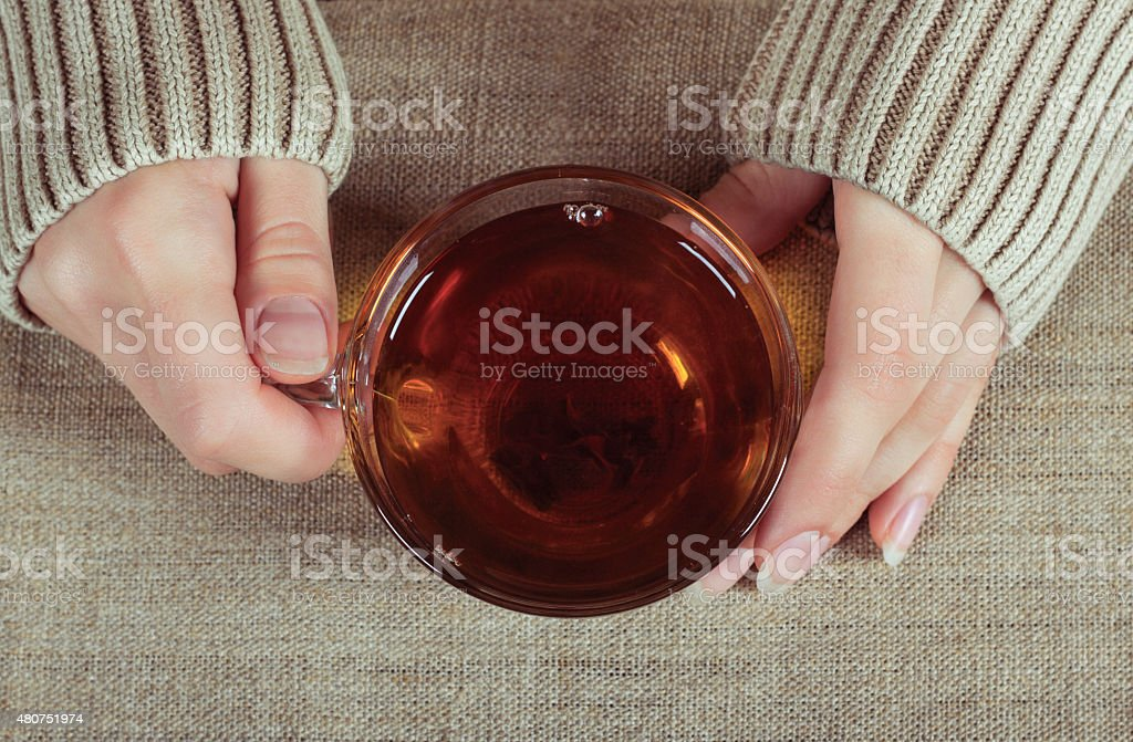 Woman hands with a cup of black tea stock photo