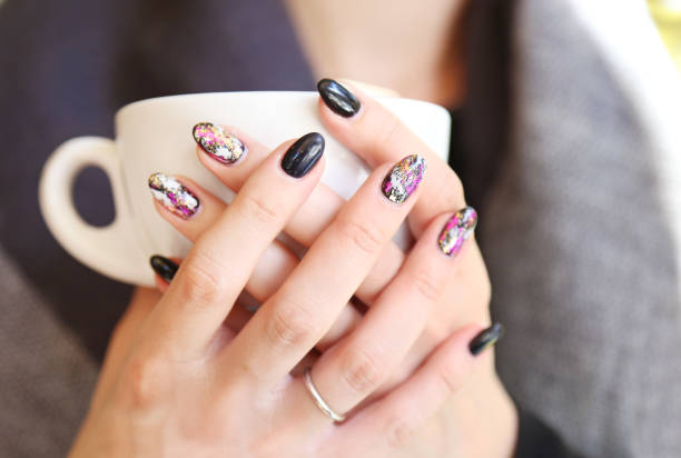 woman hands with beautiful manicure holding a cup of coffee - black polish with designed fashion shapes stock photo