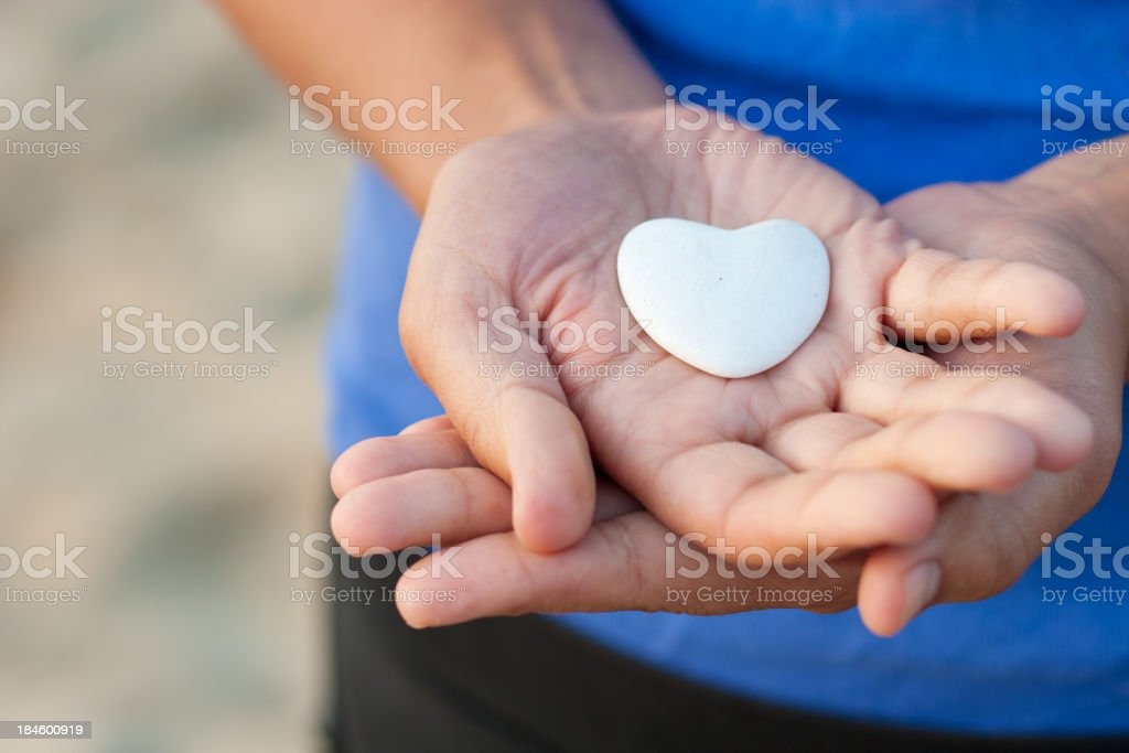 Woman hands with blue shirt showing a heart of stone. stock photo