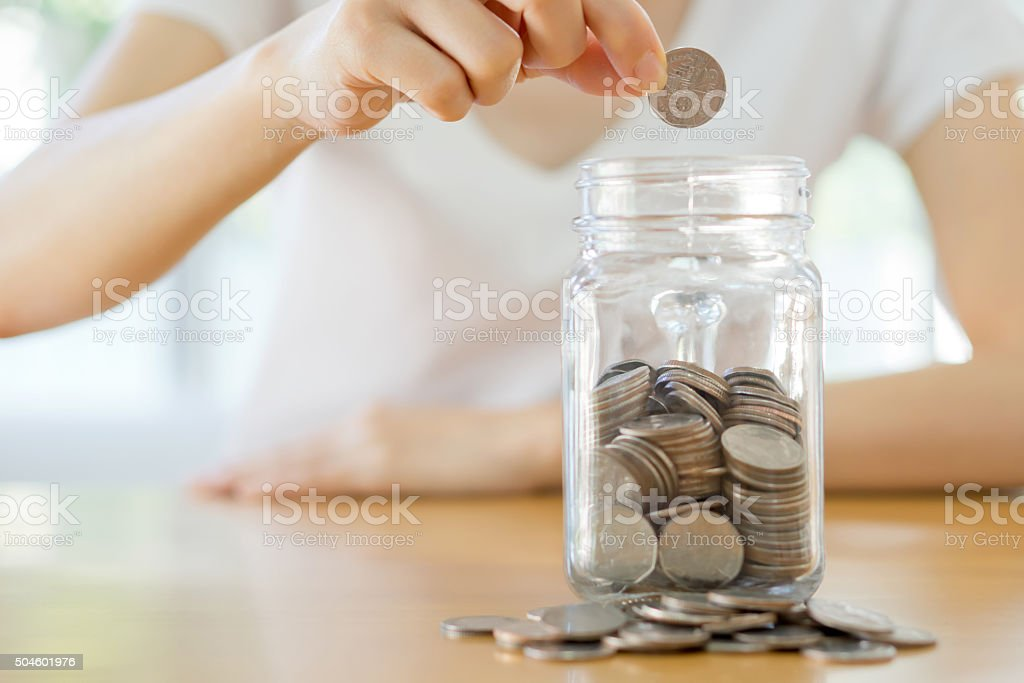 Woman hands with coins in glass jar, close up stock photo