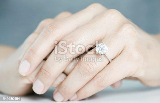 Diamond engagement ring on hands.