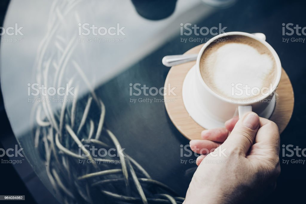 Woman hands with latte coffee on the table. - Royalty-free Adult Stock Photo