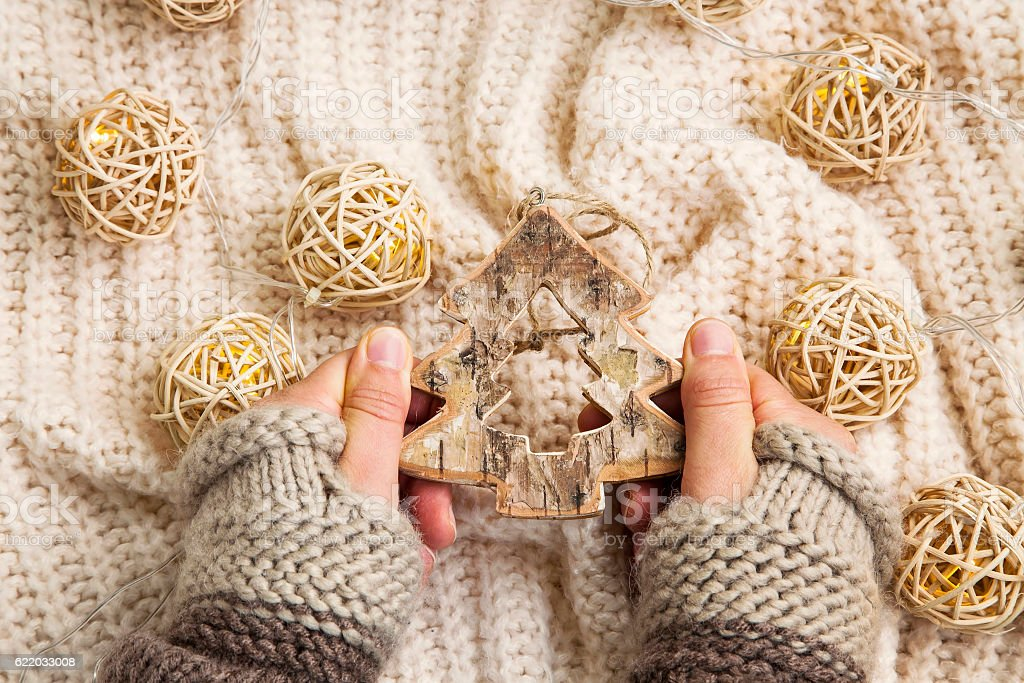 Woman hands with mittens and wooden tree xmas decoration stock photo