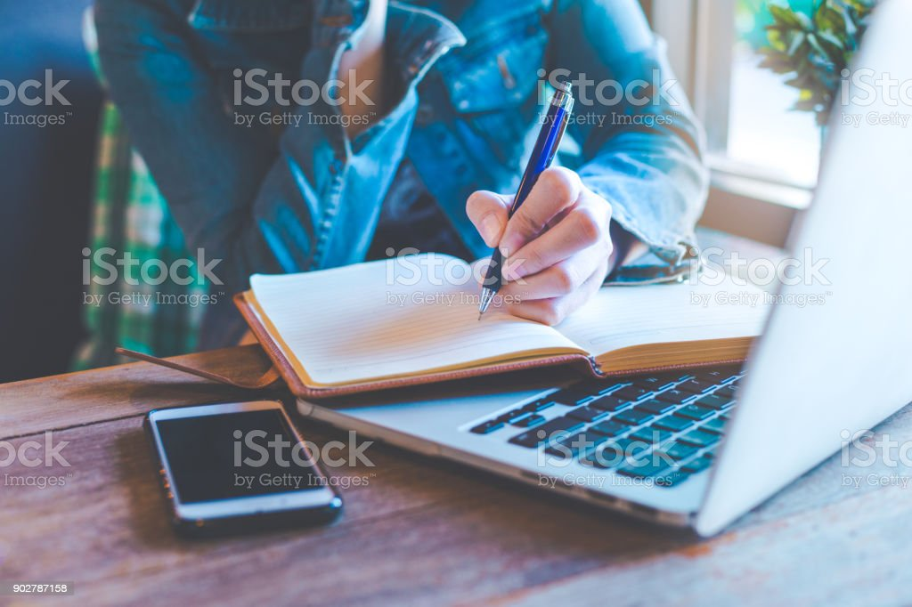 Woman hands with pen writing on notebook in the office. stock photo