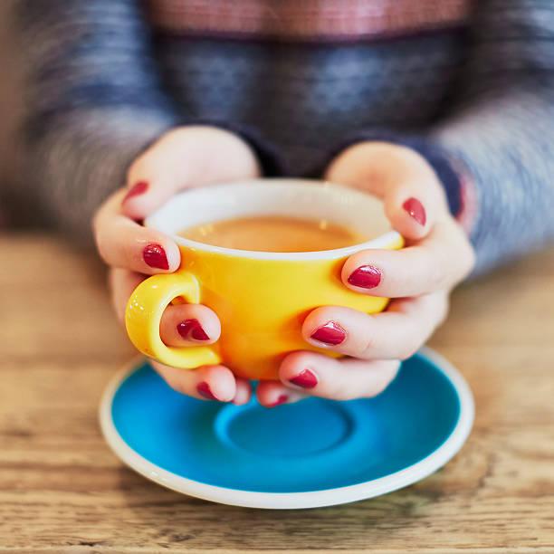 frau hände mit roten maniküre und eine tasse kaffee - herbst nagellack stock-fotos und bilder