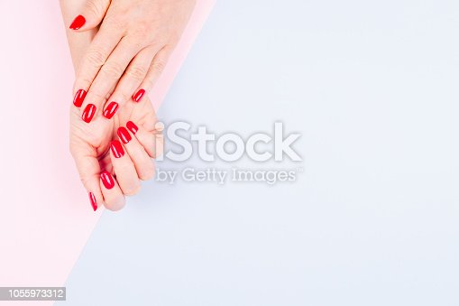 istock Woman hands with stylish red manicure on pastel blue and pink background. Holiday, party and beauty concept 1055973312