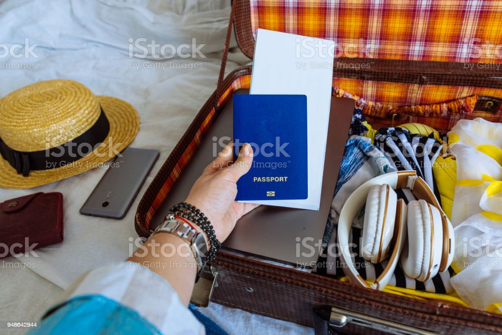 woman hands with watch put clothes in suitcase. travel concept. copy space. biometric passport laptop wallet stock photo