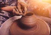 Woman hands working on pottery wheel and making a pot.