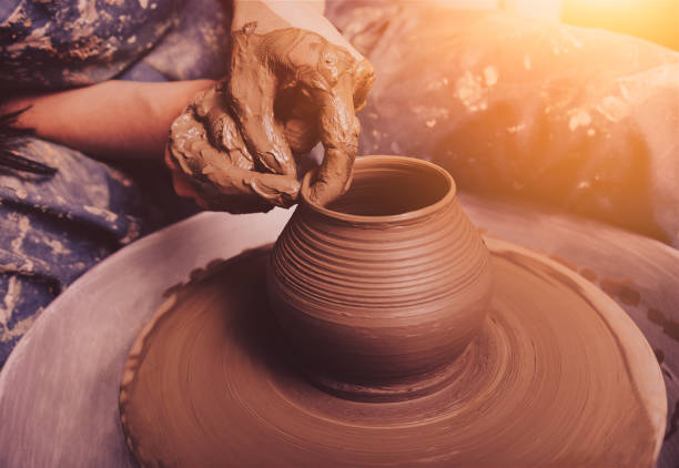 Woman hands working on pottery wheel and making a pot. Woman hands working on pottery wheel and making a pot. clay stock pictures, royalty-free photos & images