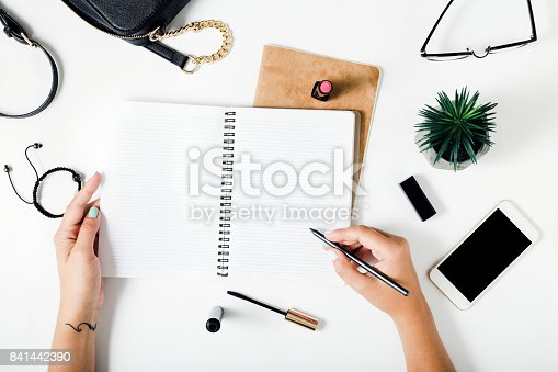 831932306 istock photo Woman hands writing in a notebook on a white table with female accessories 841442390