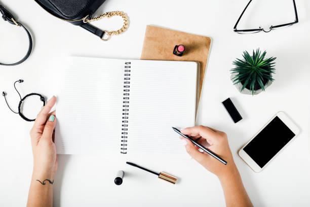 Mains de femme dans un cahier d'écriture sur un tableau blanc avec des accessoires féminins - Photo
