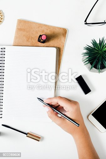 831932306 istock photo Woman hands writing in a notebook on a white table with female accessories. Concept feminine working place 922289606