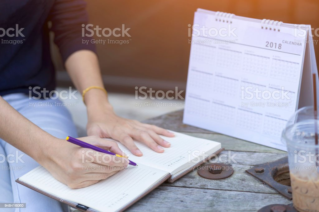 Woman hands writing plan on notebook, planning agenda and schedule using calendar event planner. Calender planner organization management remind concept. stock photo