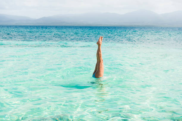 Woman handstand in turquoise sea stock photo