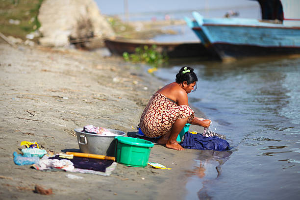 woman handwashing clothes at the riverside in myanmar - handwashing stock photos and pictures