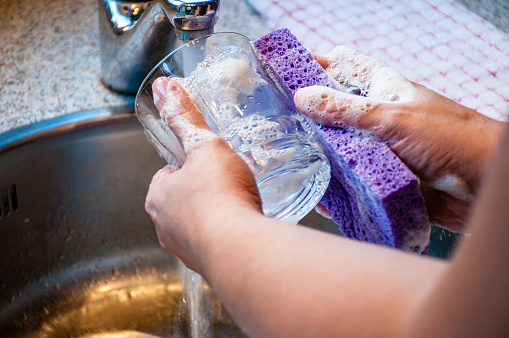 istock Woman Hand-Washing Dishes 908723294