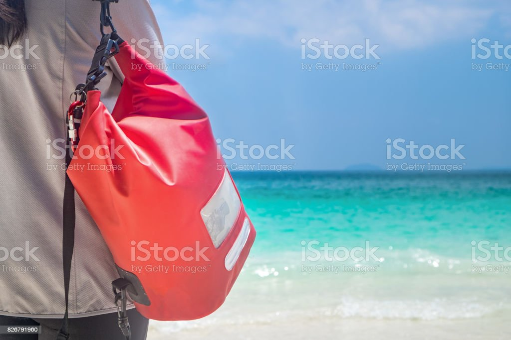 Woman Hang Dry Pack(Waterproof Luggage) on the Beach stock photo