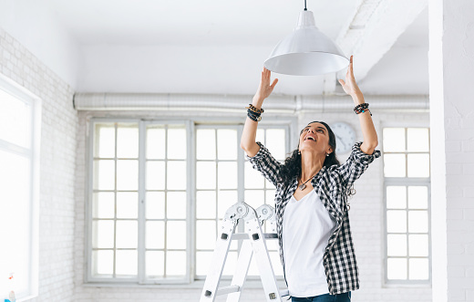 Woman hanging a lamp in new home Property Services. New Home.