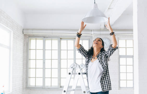 woman hanging a lamp in new home property services. new home. - decorating stock photos and pictures