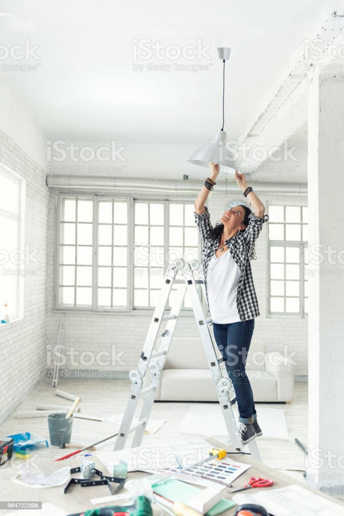 Woman hanging a lamp in new home Property Services. New Home. royalty-free stock photo
