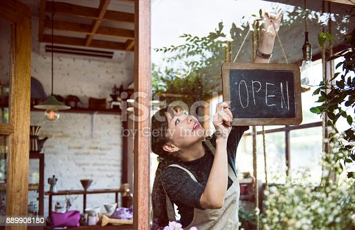 istock Woman hanging an open sign 889908180