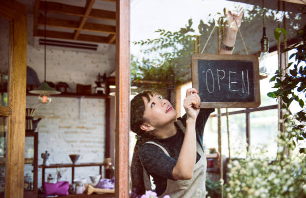 woman hanging an open sign - owner stock pictures, royalty-free photos & images