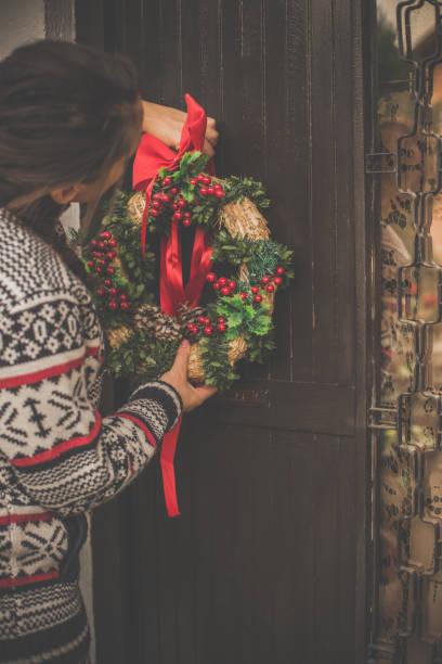 frau hängen weihnachtskranz an der haustür - deko hauseingang weihnachten stock-fotos und bilder