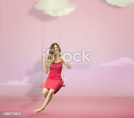 Woman hanging in a pink studio sky with clouds
