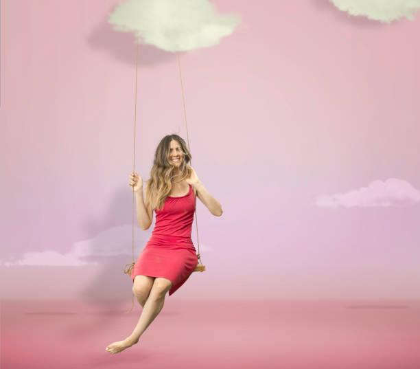 vrouw opknoping in een roze studio hemel met wolken - schommelen bungelen stockfoto's en -beelden