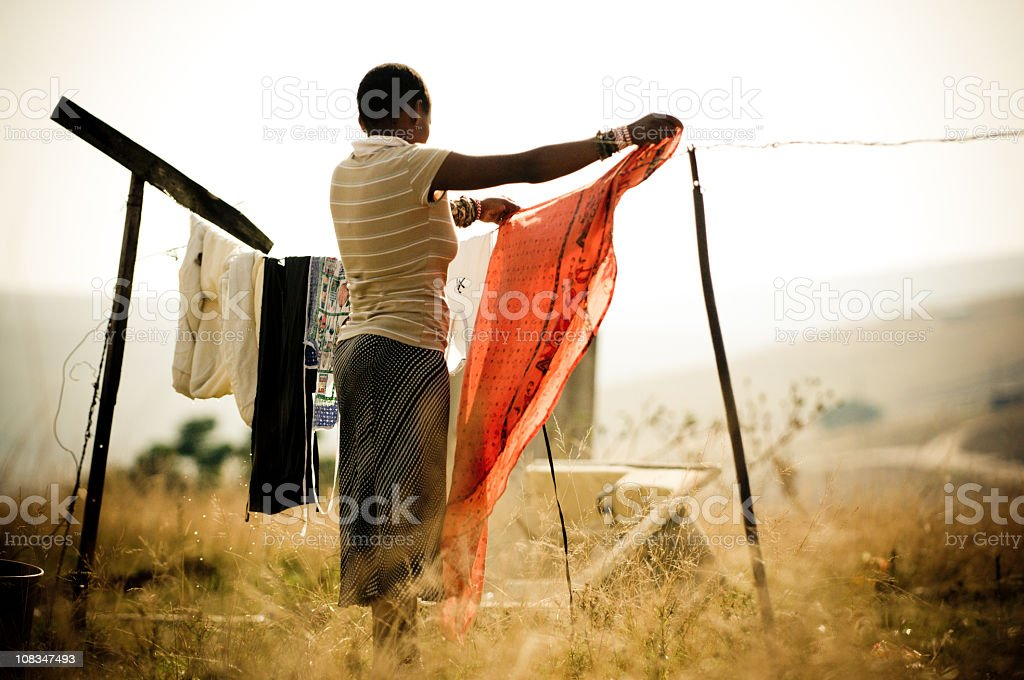 Woman hanging laundry in rural Africa stock photo