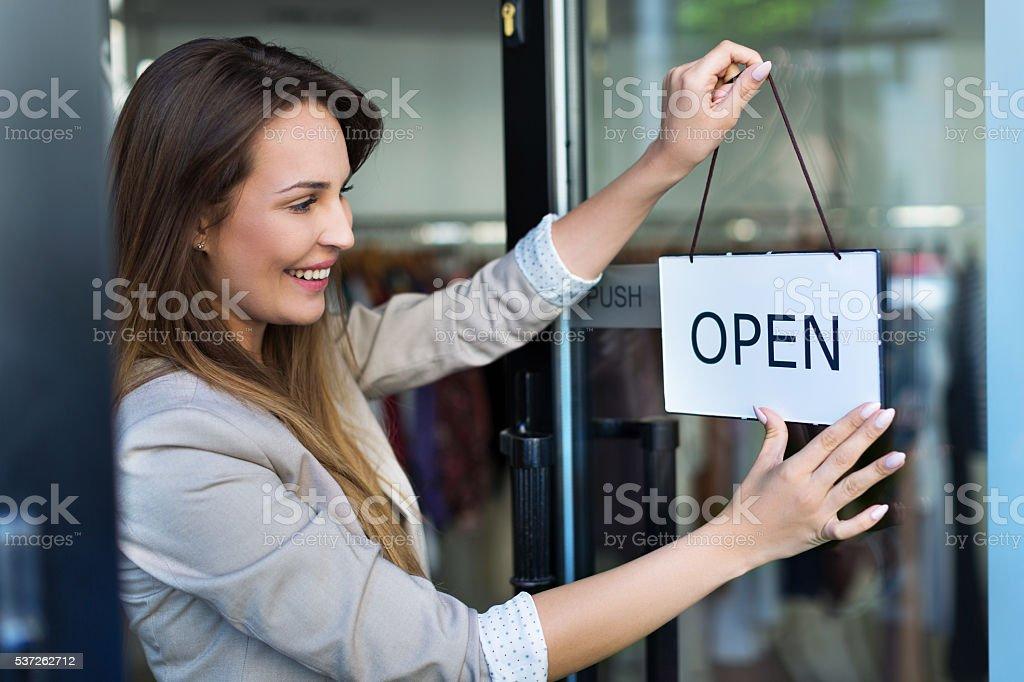 Woman hanging open sign on door stock photo