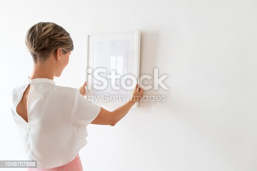 508897972 istock photo Woman hanging painting on the wall 1049707658