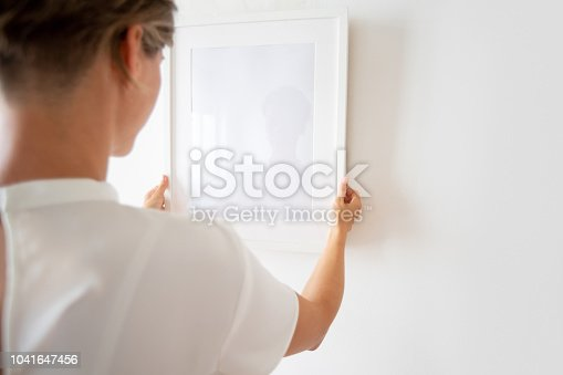 508897972 istock photo Woman hanging picture frame 1041647456