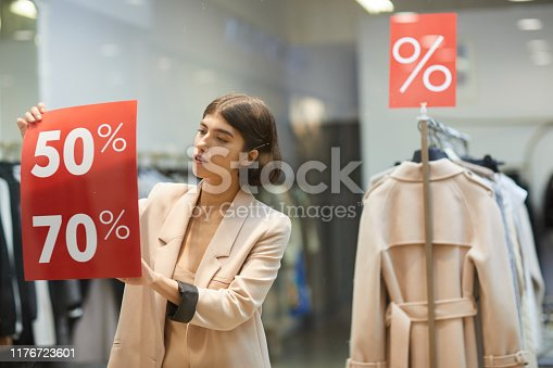 Waist up portrait of beautiful woman hanging red SALE signs on window display in clothes store, copy space