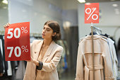 istock Woman Hanging Sale Signs in Store 1176723601