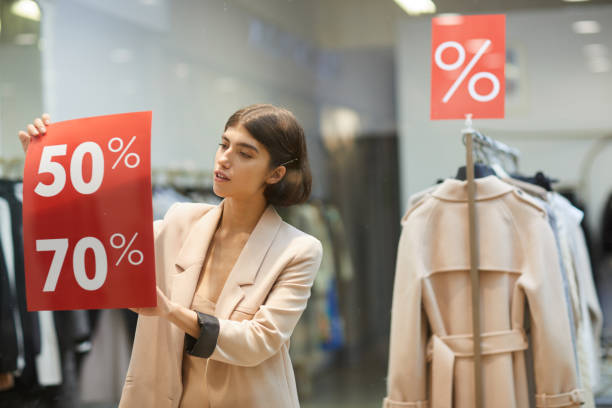 woman hanging sale signs in store - cheap stock pictures, royalty-free photos & images