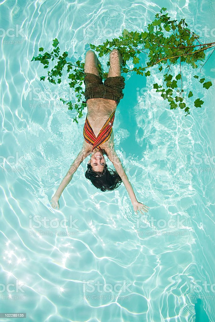 Woman hanging upside down from branch in pool
