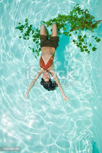 istock Woman hanging upside down from branch in pool 102285135