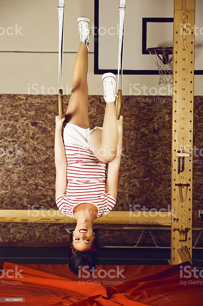 Woman hanging upside down in gymnastic rings royalty-free stock photo