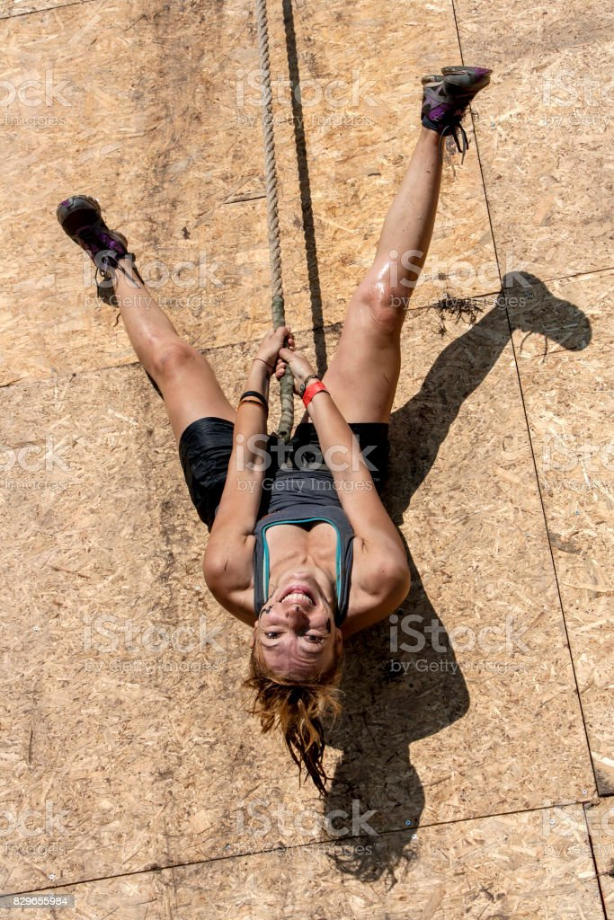 Young woman having fun and smiling; hang upside down on wooden wall...