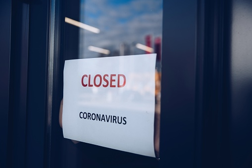 Woman hangs a card with information about the store closing on a shop window due to the coronavirus