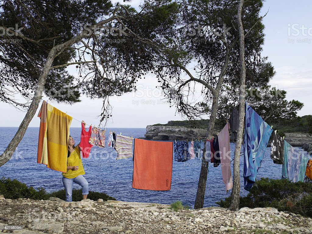 Woman hangs out clothes on lines between trees royalty free stockfoto