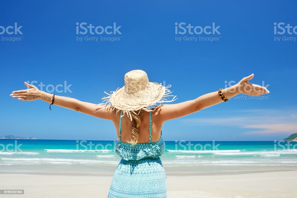 Woman happy joyful with arms up on beach in summer during holidays travel. stock photo