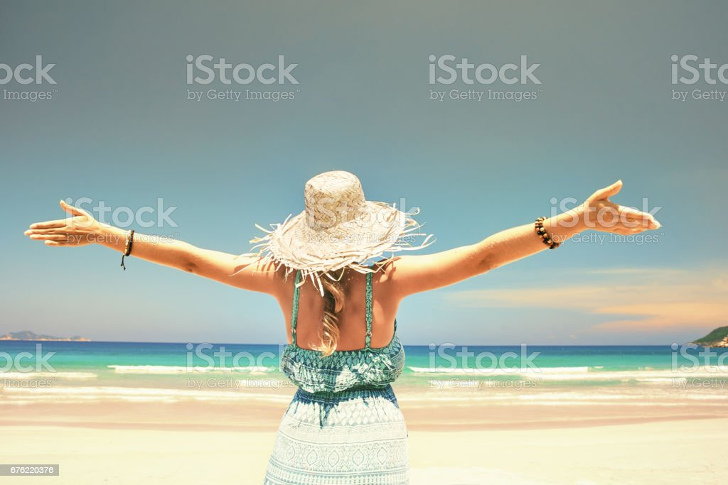 Woman happy joyful with arms up on beach in summer during holidays travel stock photo